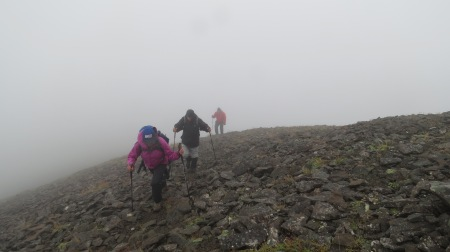 People reaching summit of unnamed mountain in fog.  This one was safe.