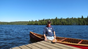 Author at Camp Pathfinder 100th year reunion, 2013, back in a red canoe for the first time in 47 years.